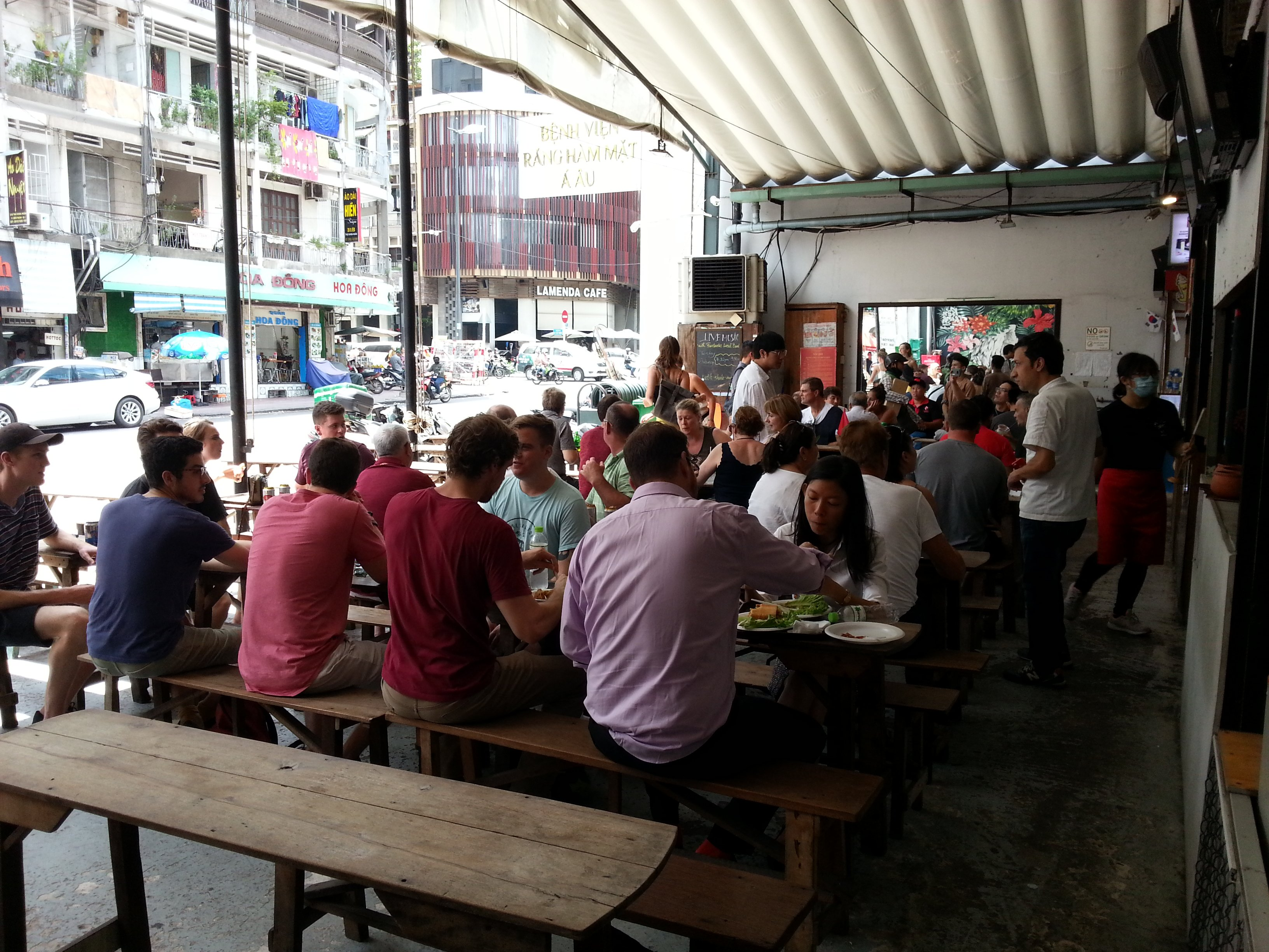 Customers sit on long tables at Ben Thanh Street Food Market